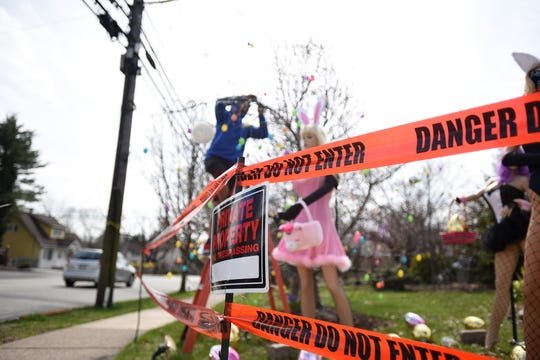 Neighbor Alex Cruz lends a helping hand to set up an Easter display on Grove Street in Clifton on Friday April 12, 2019. The original display was dismantled by a neighbor.