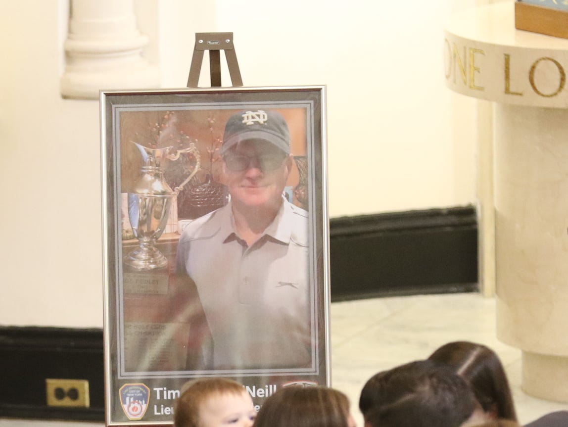 Family and friends in front of a picture of Timothy O'Neill at Sacred Heart Church for the funeral Mass held for the New York City Fire Department Lt. Timothy O'Neill. The funeral Mass was held at Sacred Heart Church in Staten Island on April 12, 2019. O'Neill died of pancreatic cancer attributed to the time he spent at Ground Zero after the attacks of September 11, 2001.