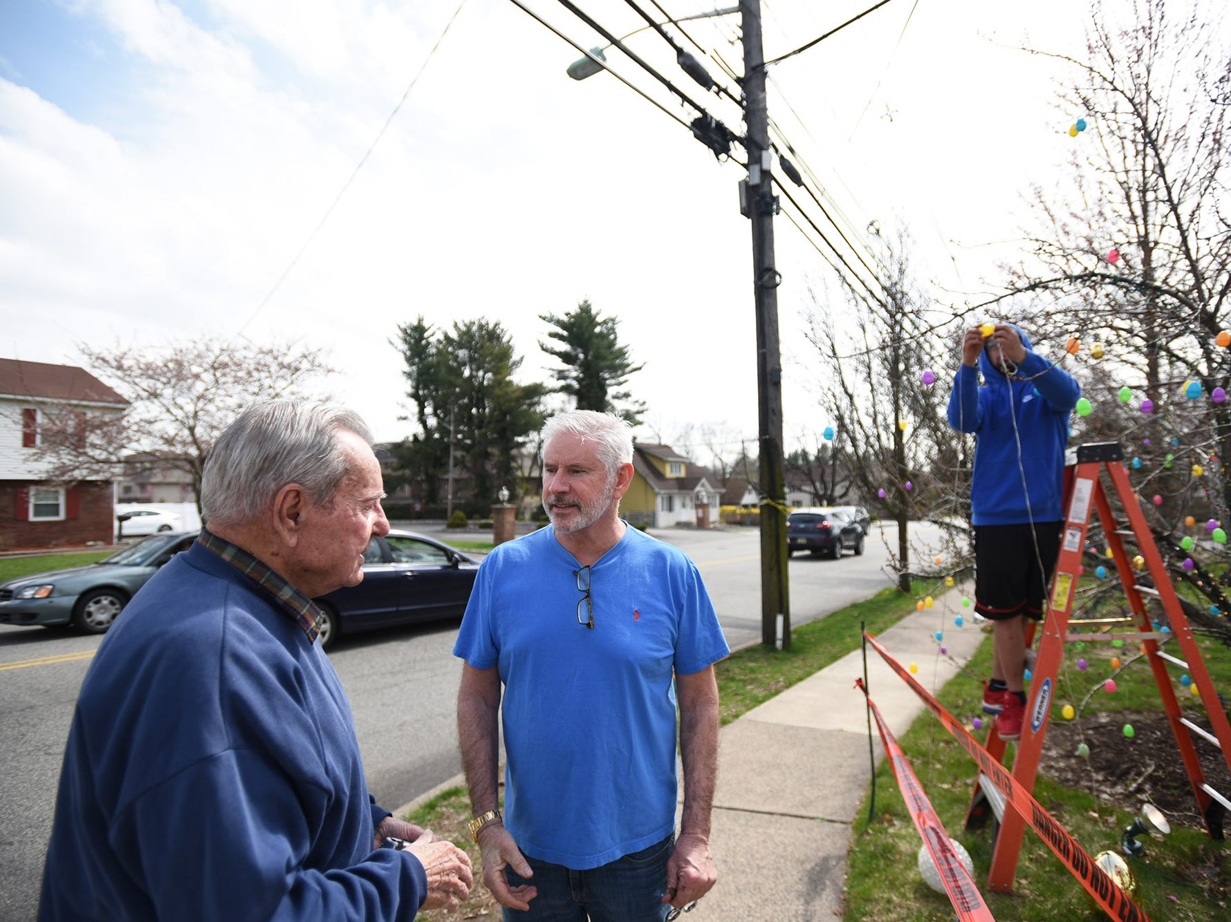 A man stops by to speak with Wayne Gangi as neighbor Alex Cruz lends a helping hand to set up an Easter display on Grove Street in Clifton on Friday April 12, 2019. The original display was dismantled by a neighbor.