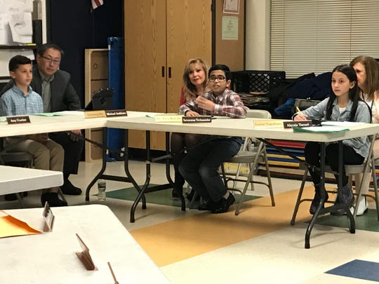 Sarvesvaran Vivekanandan, who acted as superintendent of River Edge for the night, discusses the impact of social media during a student-led school board meeting on April 10, while Superintendent  Tova Ben-Dov looks on in the background.