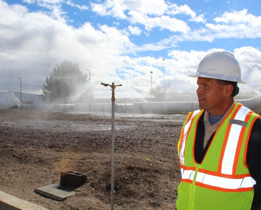 Jacob Hands Wastewater Treatment Facility Plant Manager Lorenzo Martinez surveys the reclaimed water sprinklers helping to keep moisture levels up at the facility.
