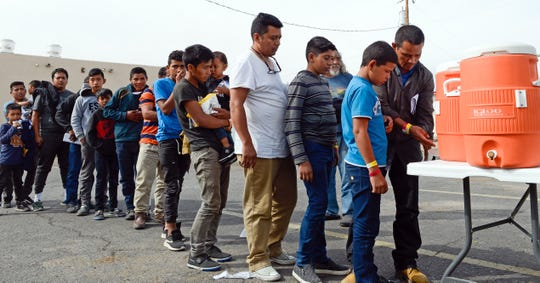 Migrants wait in line to get drinks after being dropped off by the Border Patrol at the Gospel Rescue Mission in Las Cruces on Friday morning, April 12, 2019.