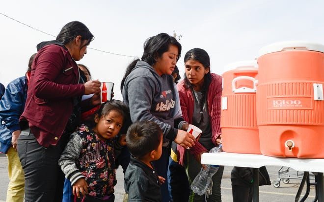 Migrants get drinks after being dropped off at the Gospel Rescue Mission in Las Cruces on Friday, April 12, 2019.