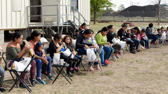Migrants dropped off by the Border Patrol at the Gospel Rescue Mission in Las Cruces eat bag lunches outside the shelter on Friday, April 12, 2019.