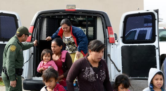 A Border Patrol agent helps migrants out of a van at the Gospel Rescue Mission in Las Cruces on Friday morning, April 12, 2019.