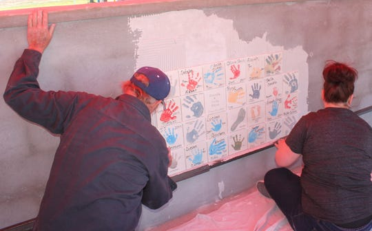 Craig Danekas and Jessica Heidel place tiles on the new handprint wall at Kids Zone park on April 6.