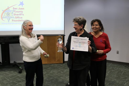 San Juan Court Appointed Special Advocates (CASA) Program Director Amy O'Neil poses with Beckie Adams, middle, Stella Cly, right, as Adams holds the  Group Winner award during the San Juan College Annual Volunteer Recognition Awards Reception held Thursday afternoon in the Henderson Fine Arts Center.