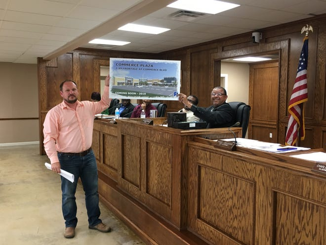 Derrick Comeaux, a marketing officer for an investment group seeking to locate a strip mall in Opelousas off Interstate 49, holds up a drawing of the plans for the development which could begin in June. Helping Comeaux with the display is Mayor Julius Alsandor.