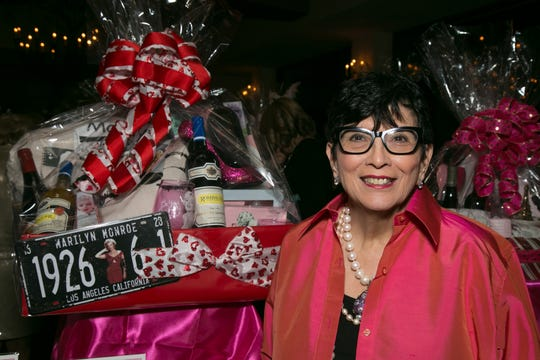 Mary Fromberg poses with one of the 19 spectacular wine gift baskets she created for the silent auction.