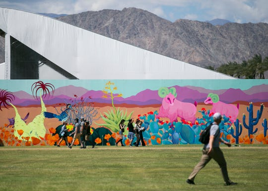 Festival goers walk past a mural at the Coachella Valley Music and Arts Festival in Indio, Calif. on Fri. April 12, 2019.