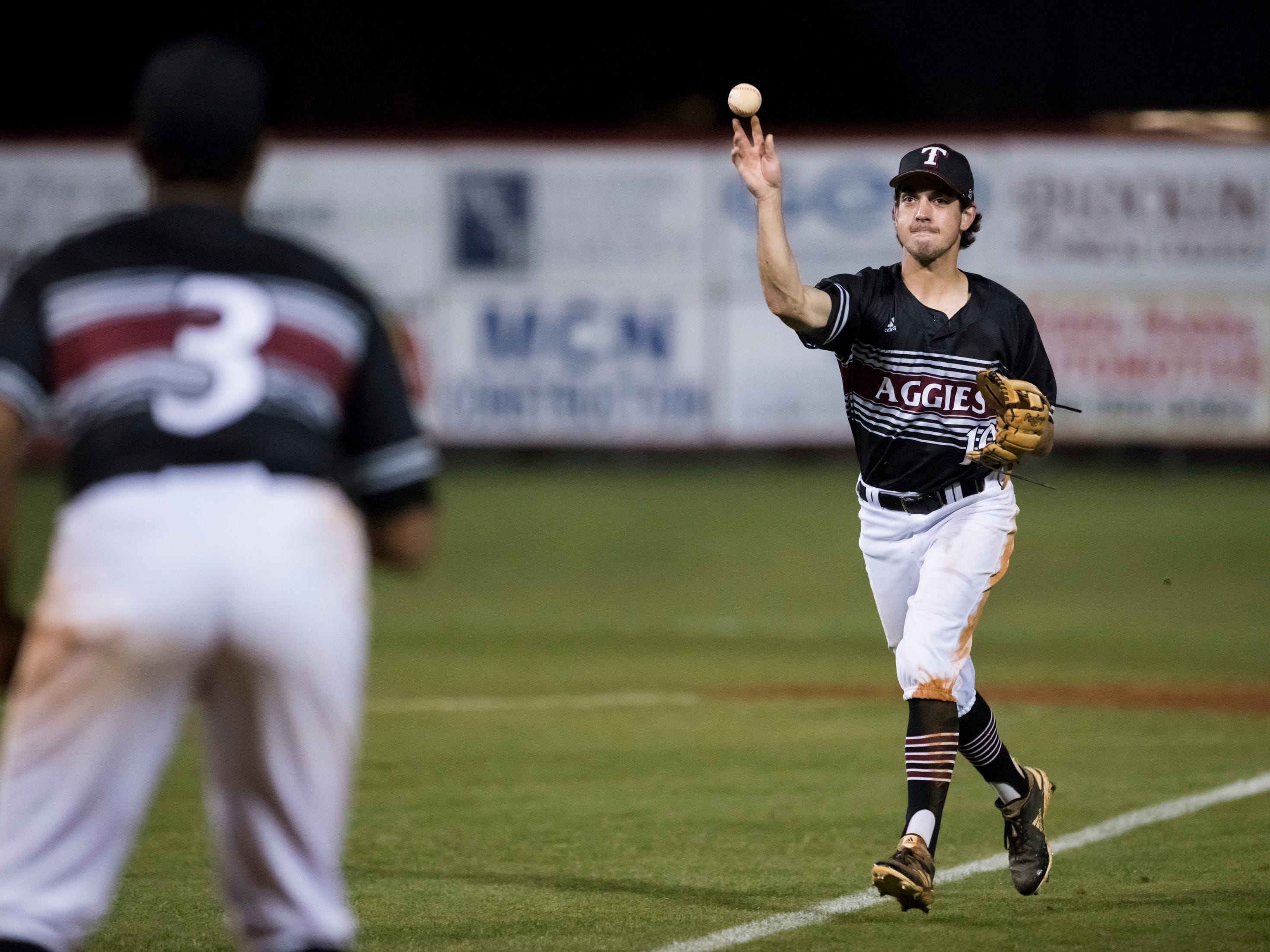 Hunter McLean (10) tosses to first for an out during the Tate vs Pace baseball game at Pace High School on Thursday, April 11, 2019.