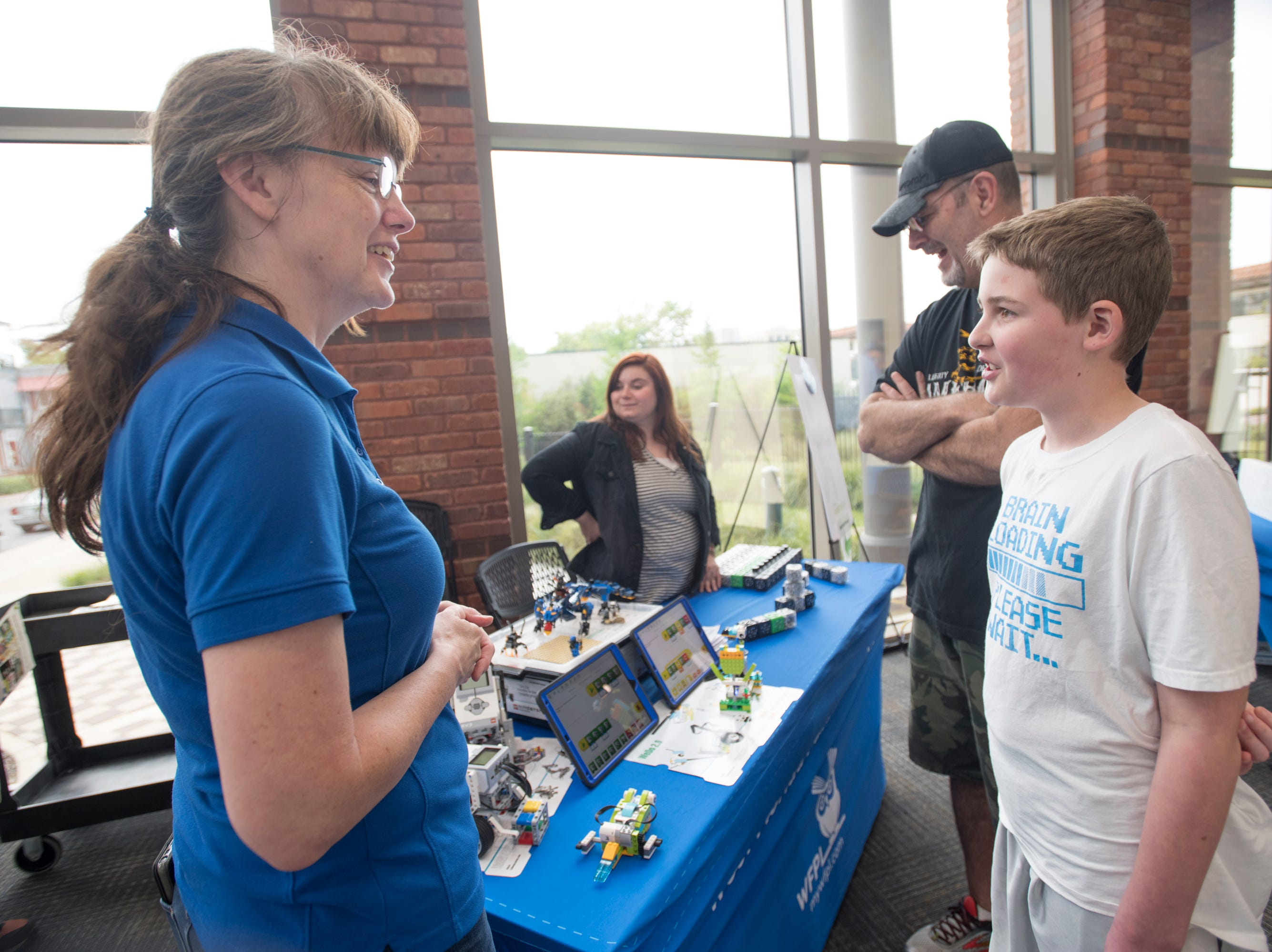 West Florida Public Libraries senior librarian Kimberly Ball, left, chats with Dane Bullock, 12, during the IHMC Open House in downtown Pensacola on Friday, April 12, 2019.