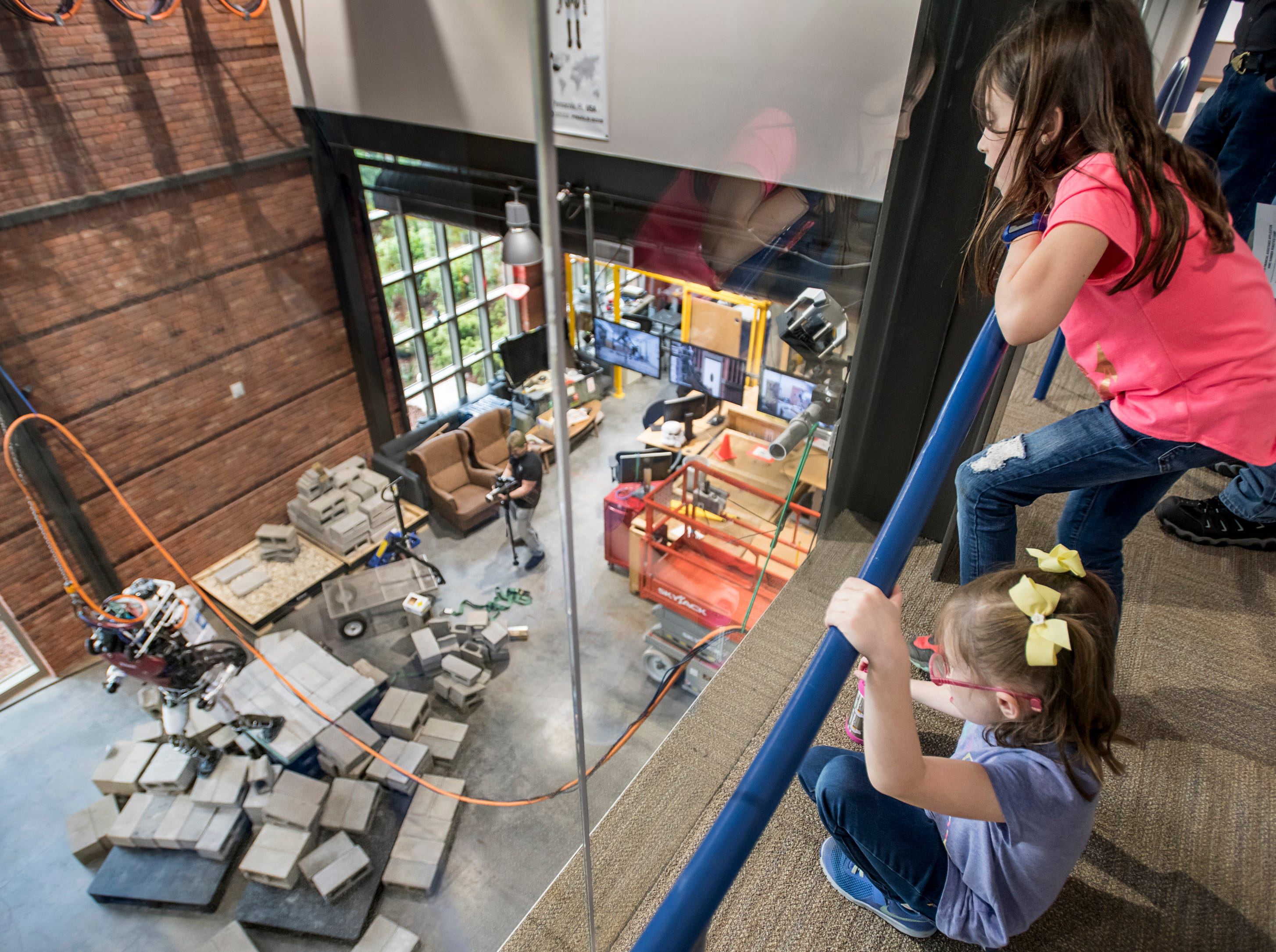 Renee McShane, 10, top, and her sister Madelyn McShane, 7, watch a demonstration of the Atlas robot during the IHMC Open House in downtown Pensacola on Friday, April 12, 2019.
