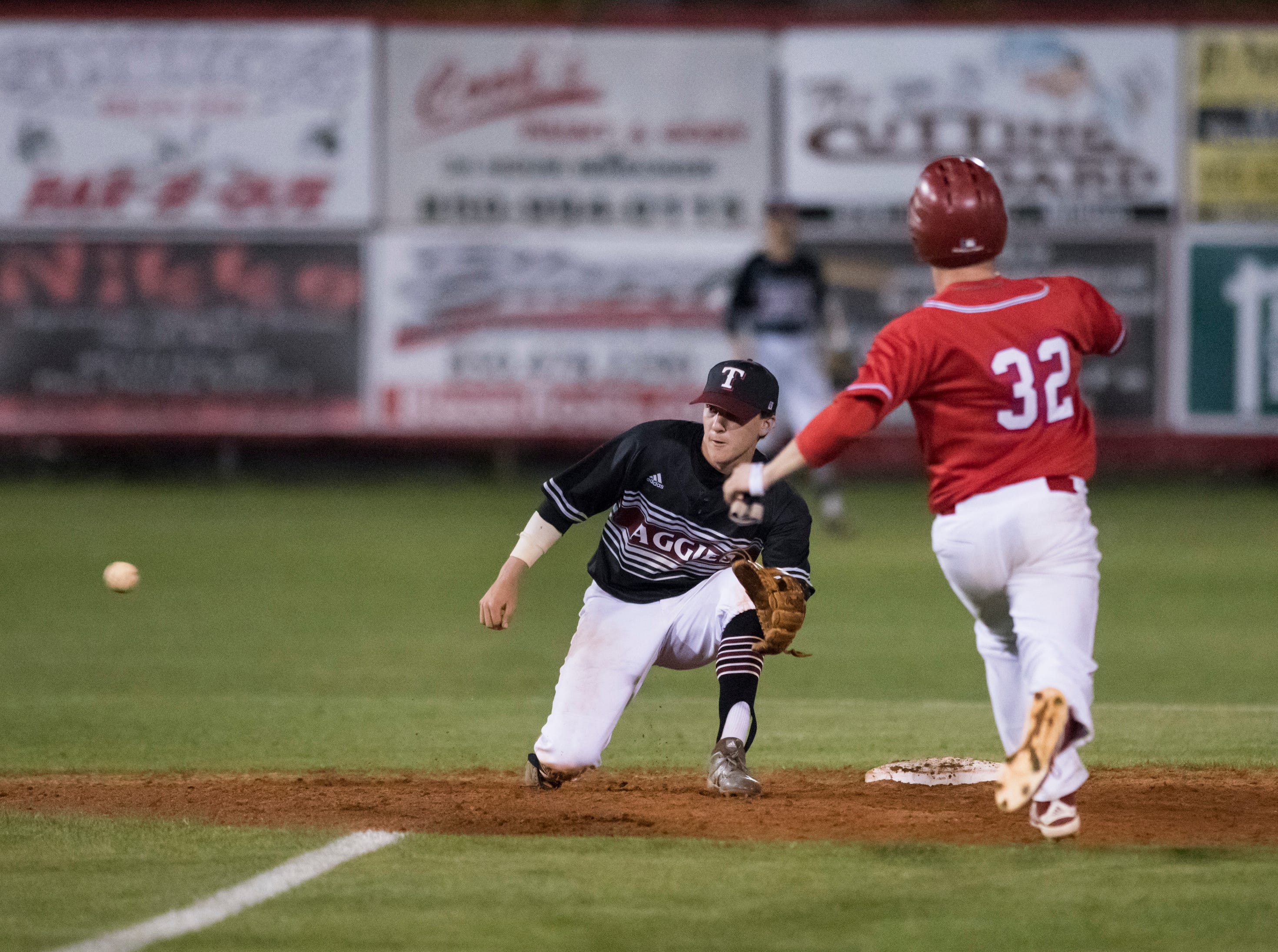 Shortstop Mason Land (9) gets for the throw before tagging Kobe Hesters (32) out as he attempts to steal second base during the Tate vs Pace baseball game at Pace High School on Thursday, April 11, 2019.