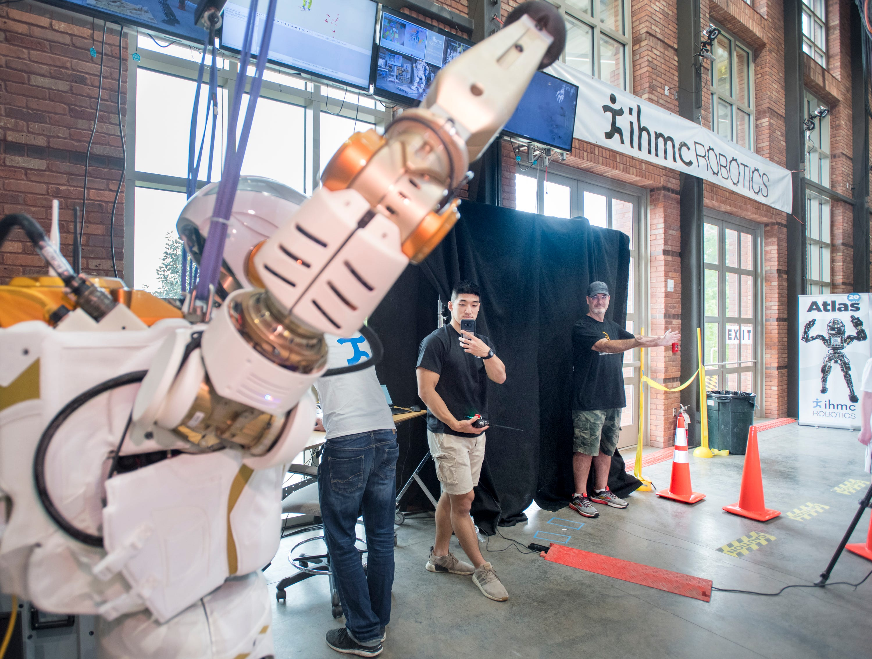 Derry Bullock, right, watches as the Valkyrie robot mimics his arm gestures during the IHMC Open House in downtown Pensacola on Friday, April 12, 2019.
