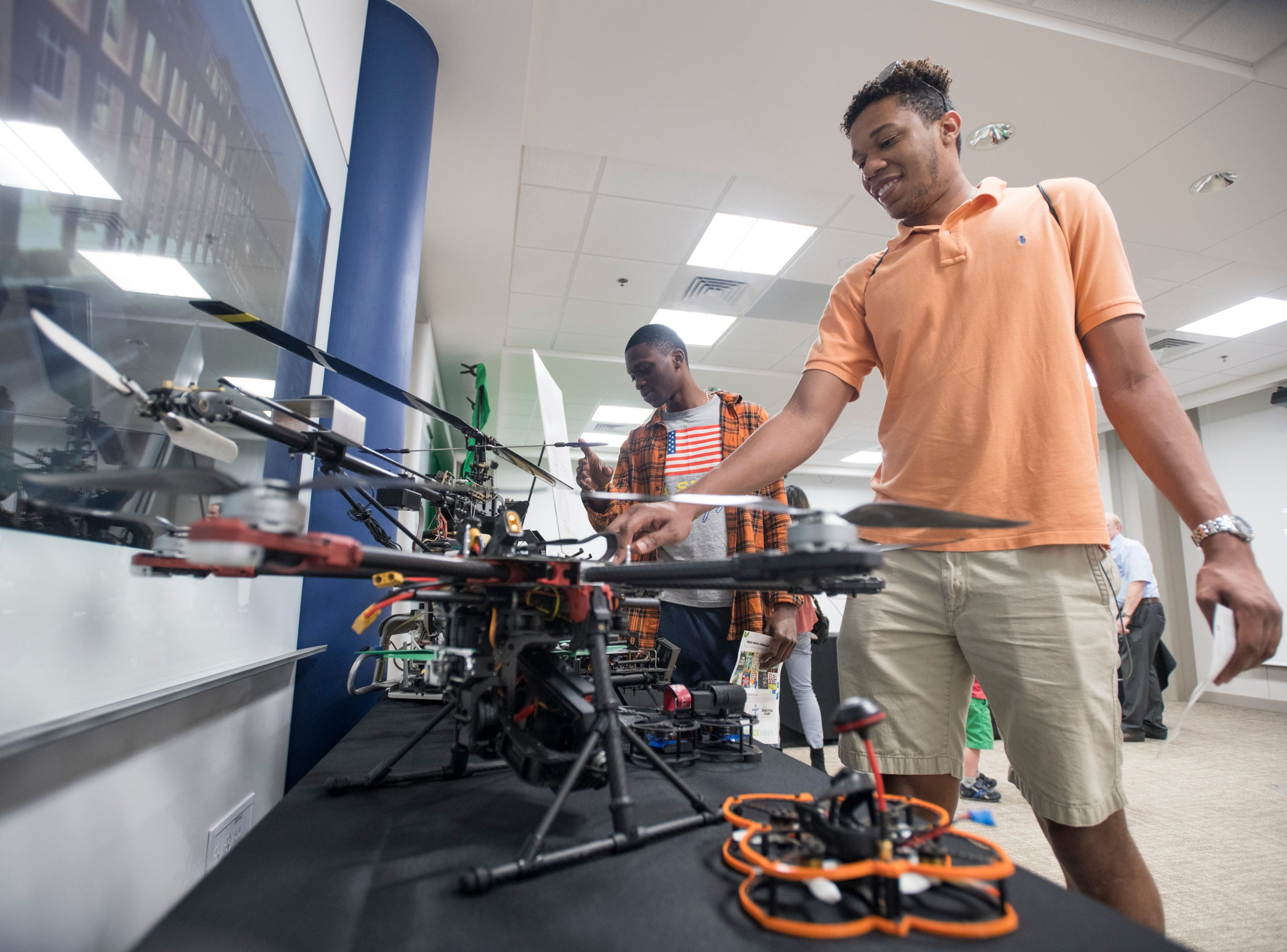 FSU engineering students Newton St. Louis, left, and Tarick Walcott check out drones on display during the IHMC Open House in downtown Pensacola on Friday, April 12, 2019.