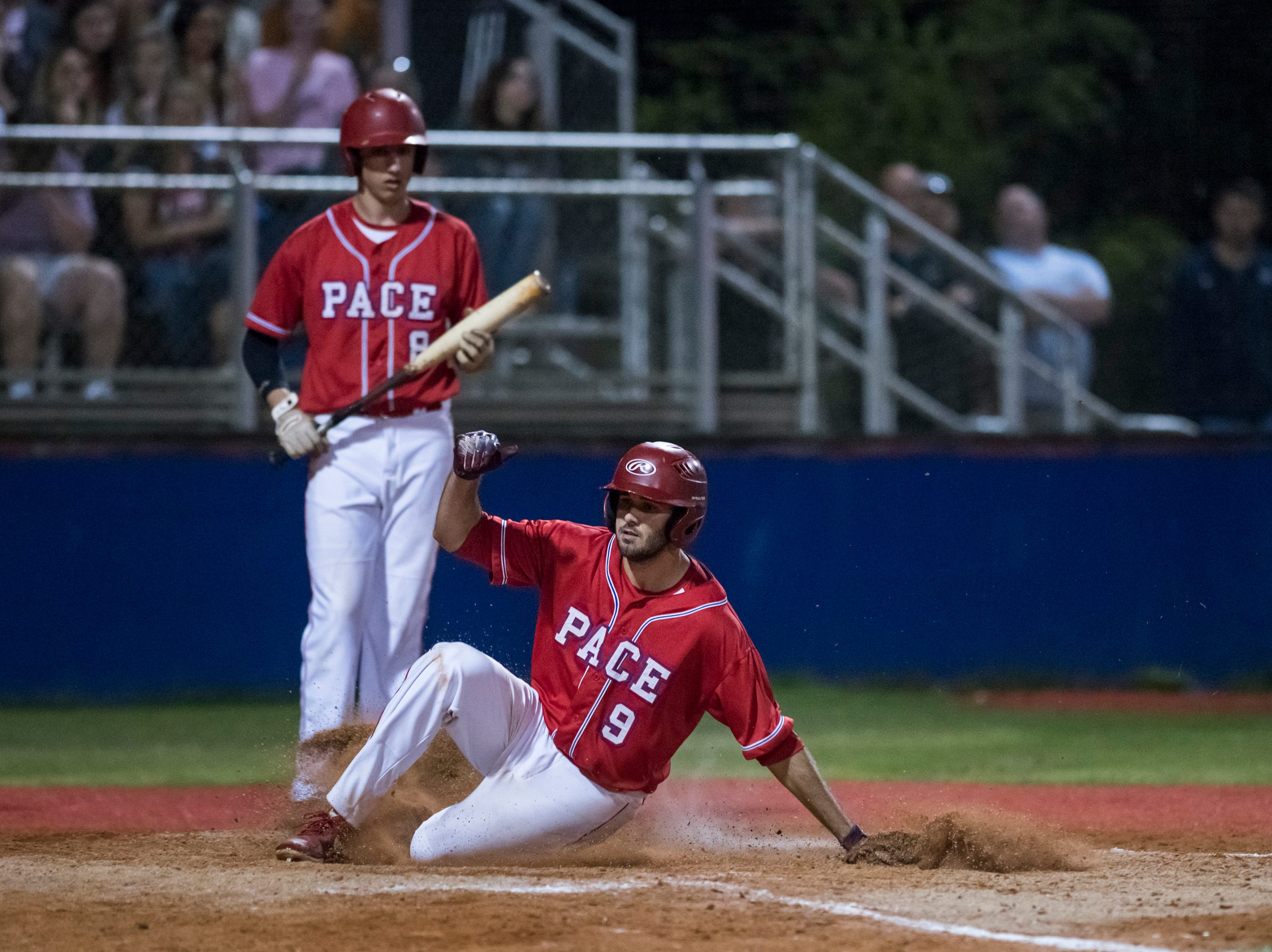 Dalton Dean (9) slides home on a pitch that got past the catcher cutting the Aggie lead to 5-1 during the Tate vs Pace baseball game at Pace High School on Thursday, April 11, 2019.