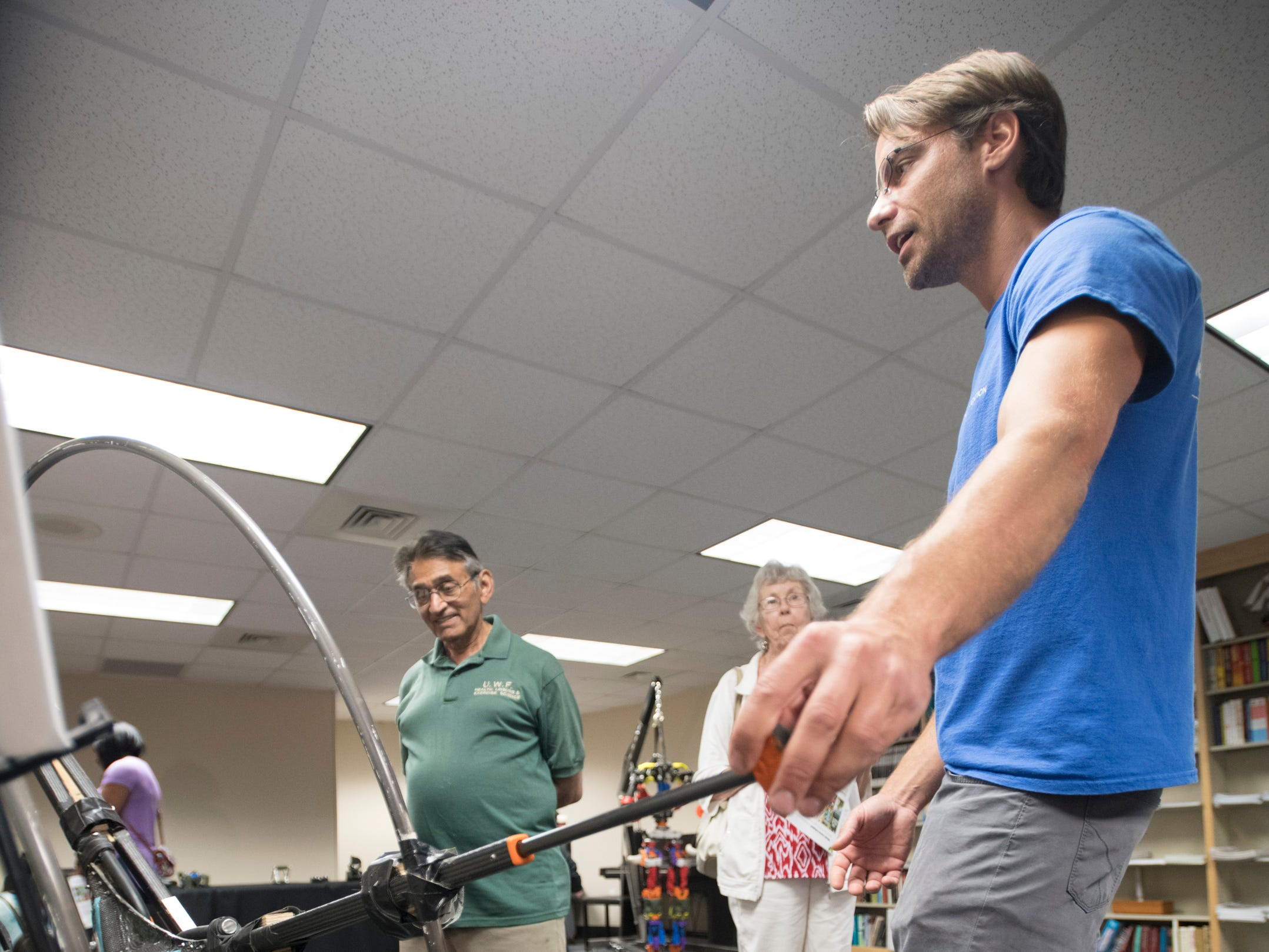 Research scientist Chris Schmidt-Wetekam, right, talks about running robots during the IHMC Open House in downtown Pensacola on Friday, April 12, 2019.