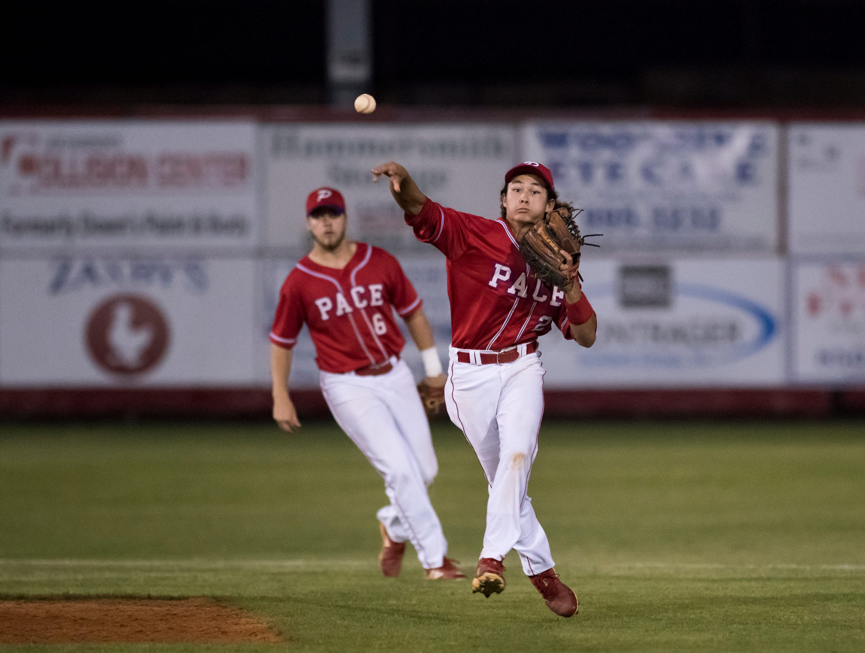 Caleb Vincent (24) errantly throws to first base during the Tate vs Pace baseball game at Pace High School on Thursday, April 11, 2019.