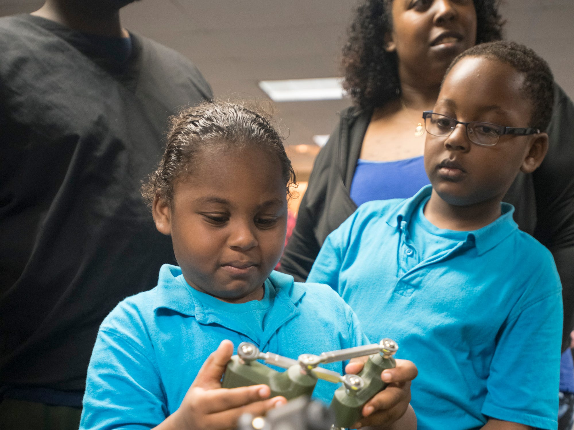 Joahua Mosley, 6, left, and Justin Mosley Jr. 7, check out mechanical parts during the IHMC Open House in downtown Pensacola on Friday, April 12, 2019.
