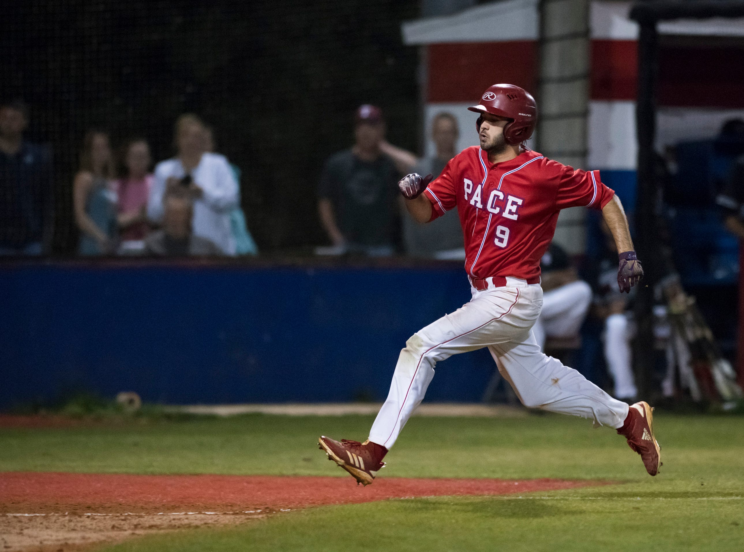 Dalton Dean (9) heads home on a pitch that got past the catcher cutting the Aggie lead to 5-1 during the Tate vs Pace baseball game at Pace High School on Thursday, April 11, 2019.