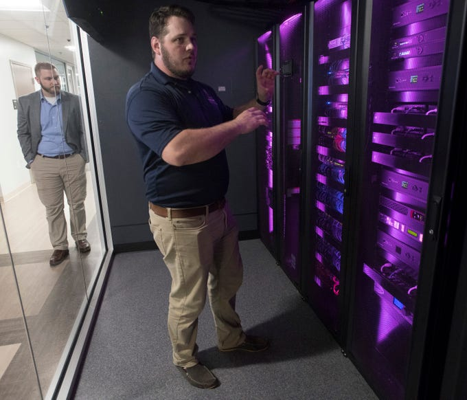Chad Hoye, systems network assistant, describes the network and the Center for Cybersecurity's centerpiece of technology he helped to build during a tour of the new University of West Florida facility on Friday, April 12, 2019. Located in the Studer Community Institute building the new UWF center will increase the university's presence in downtown Pensacola.