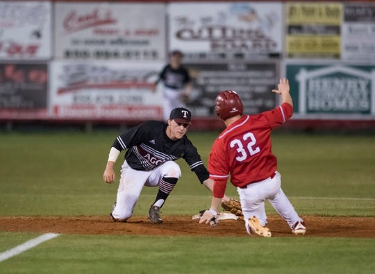Shortstop Mason Land (9) tags out Kobe Hesters (32) as he attempts to steal second base during the Tate vs Pace baseball game at Pace High School on Thursday, April 11, 2019.