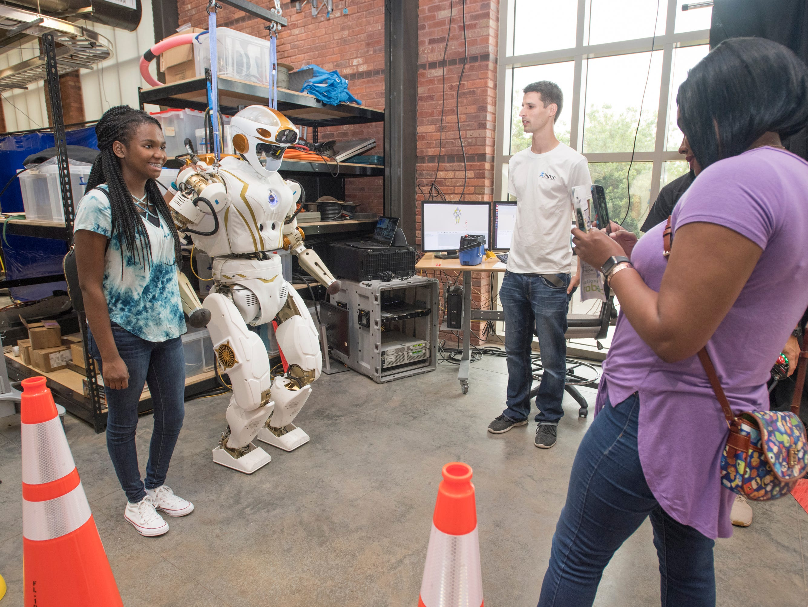 Danielle Diggs snaps a photo of her sister Destinie Diggs, 16, as she poses with the Valkyrie robot during the IHMC Open House in downtown Pensacola on Friday, April 12, 2019.