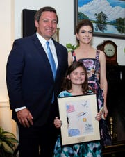 "Gulf Breeze Elementary School student Whitney Morrill poses for a photo with Gov. Ron DeSantis and Florida First Lady Casey DeSantis at the governor's mansion in Tallahassee to honor Morrill's state-award winning drawing of Gen. Daniel ""Chappie"" James."