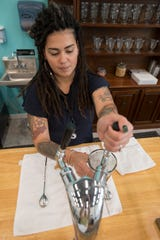 Cristi Fonseca Ramirez, co-owner of Old City Market Inc., on Jefferson Street prepares a butterscotch fountain drink on Friday.