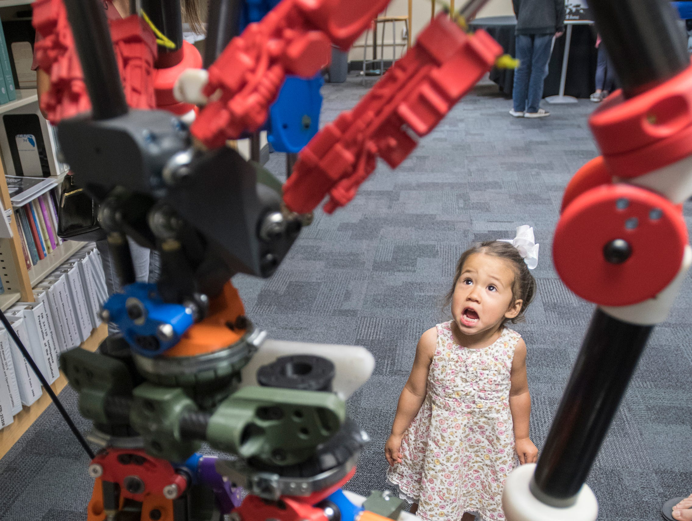 2 1/2 year old Nova Butler checks out the humanoid robot called Nadia during the IHMC Open House in downtown Pensacola on Friday, April 12, 2019.  Nadia is a gymnast-inspired robot with hydraulic actuators.