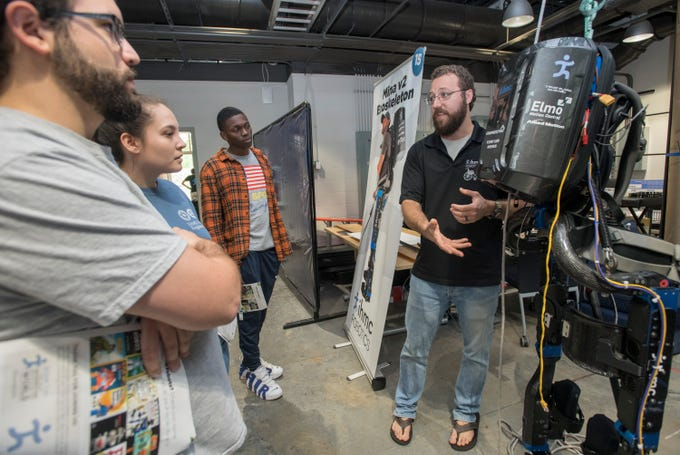 Travis Craig, right, talks about Exoskeletons during the IHMC Open House in downtown Pensacola on Friday, April 12, 2019.