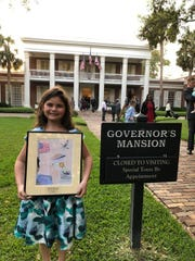 "Gulf Breeze Elementary School student Whitney Morrill poses for a photo at the governor's mansion in Tallahassee for her state-award winning drawing of Gen. Daniel ""Chappie"" James."