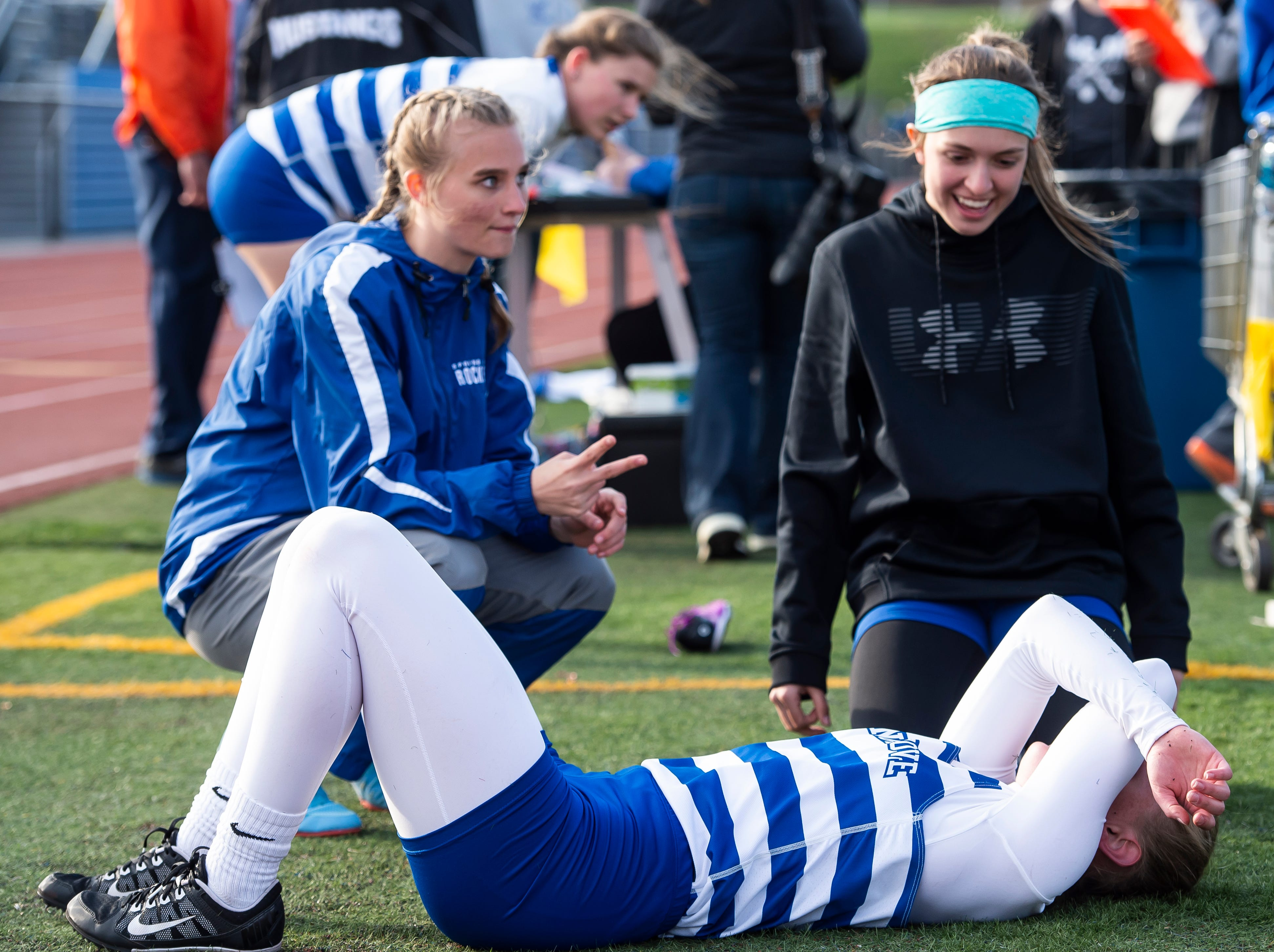 A Spring Grove athlete rests on the turf after competing in the 800m during a track and field meet on Thursday, April 11, 2019.