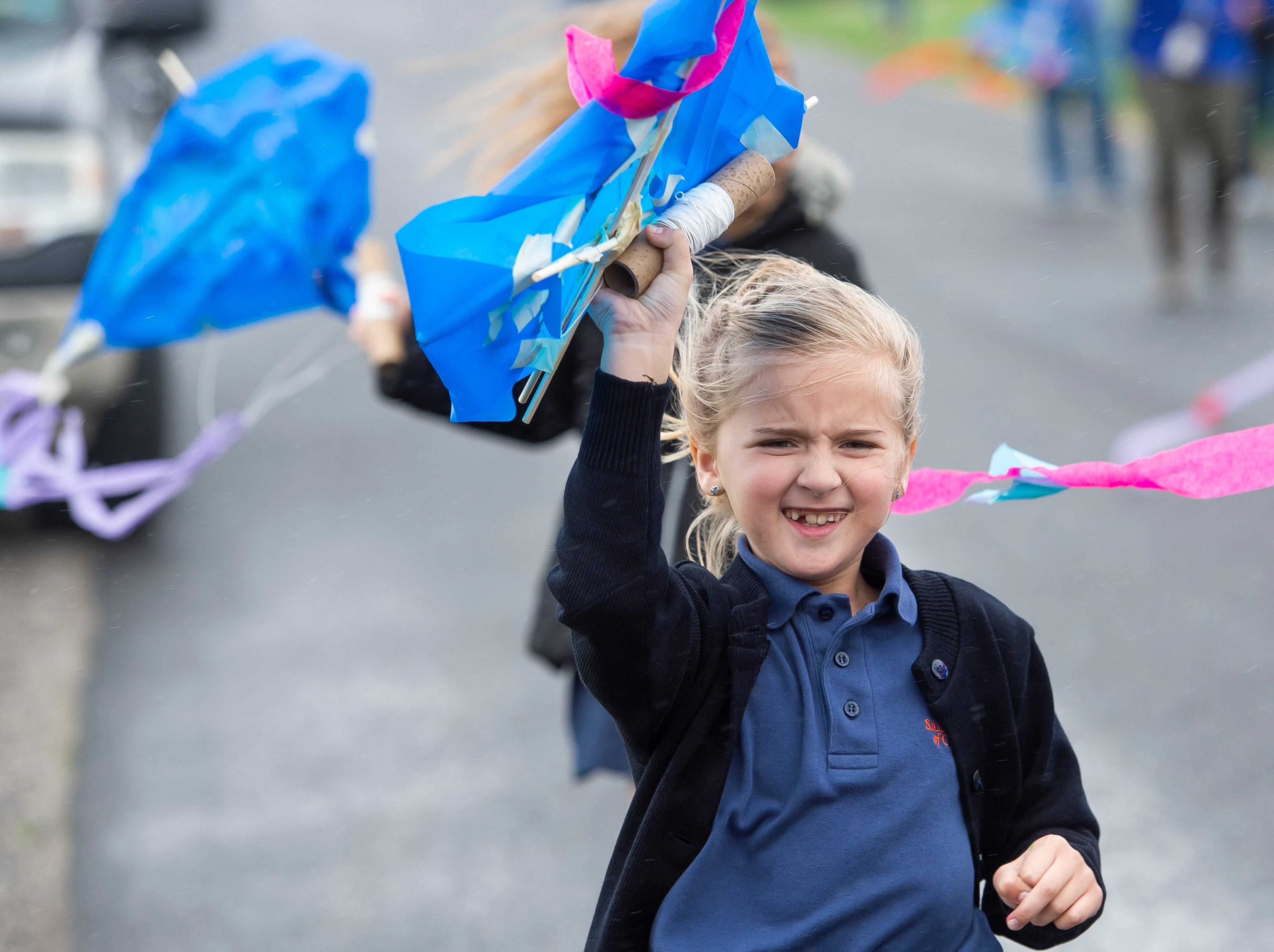Students from St. Teresa of Calcutta Catholic School use their homemade kites to shield themselves from the rain at the school's Conewago campus on Friday, April 12, 2019.