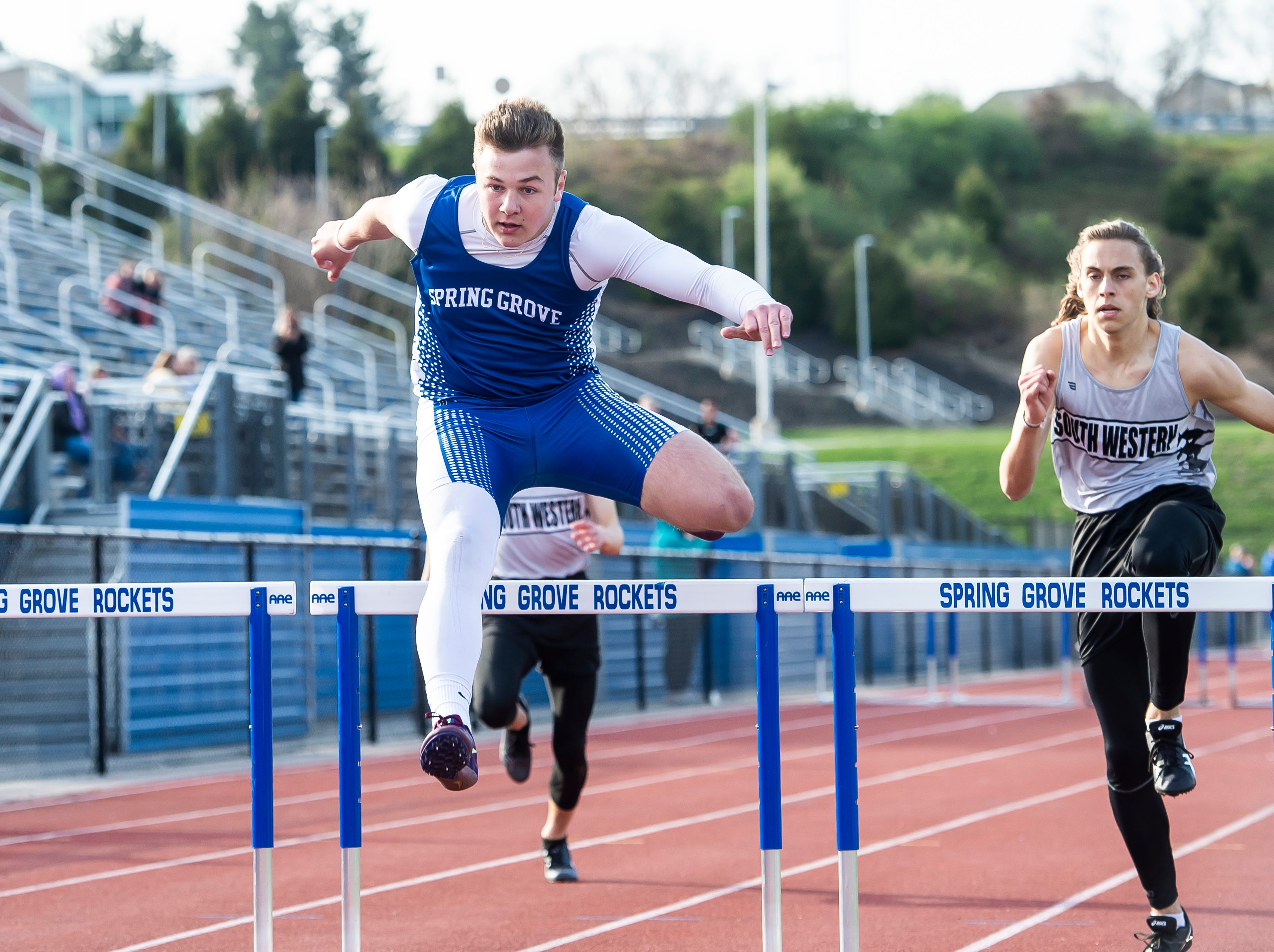 Spring Grove's Jonah Warehime leaps over the final hurdle in the 300m hurdles on his way to place first during a track and field meet against South Western on Thursday, April 11, 2019.
