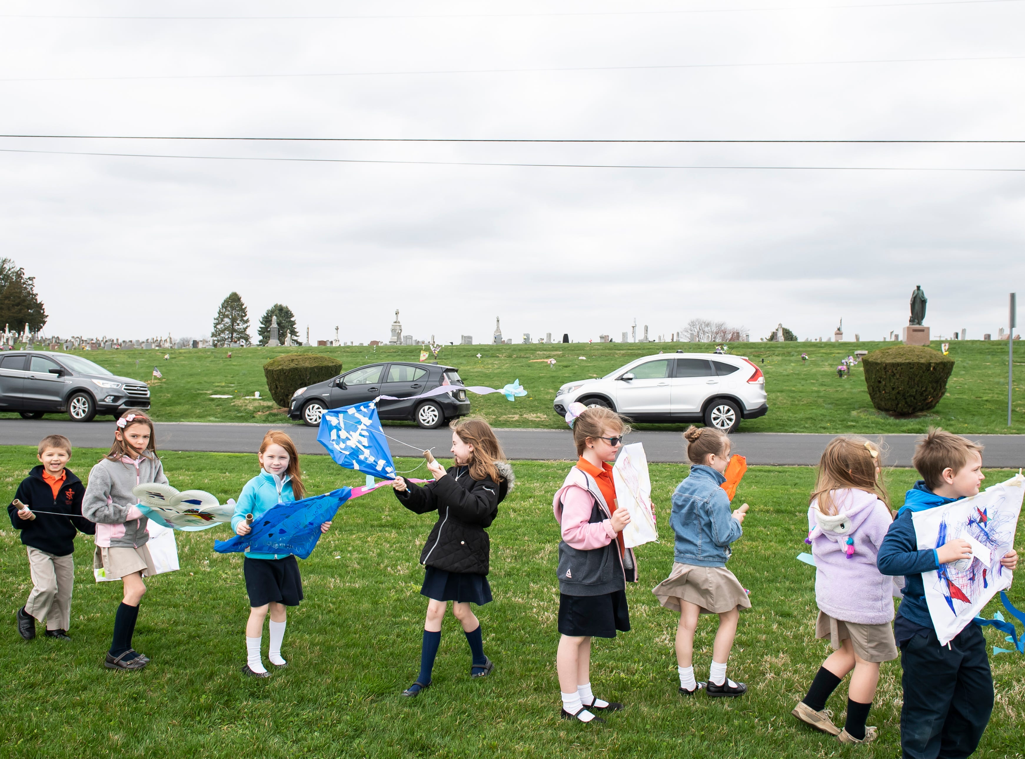 Students from St. Teresa of Calcutta Catholic School prepare to fly their homemade kites at the school's Conewago campus on Friday, April 12, 2019.