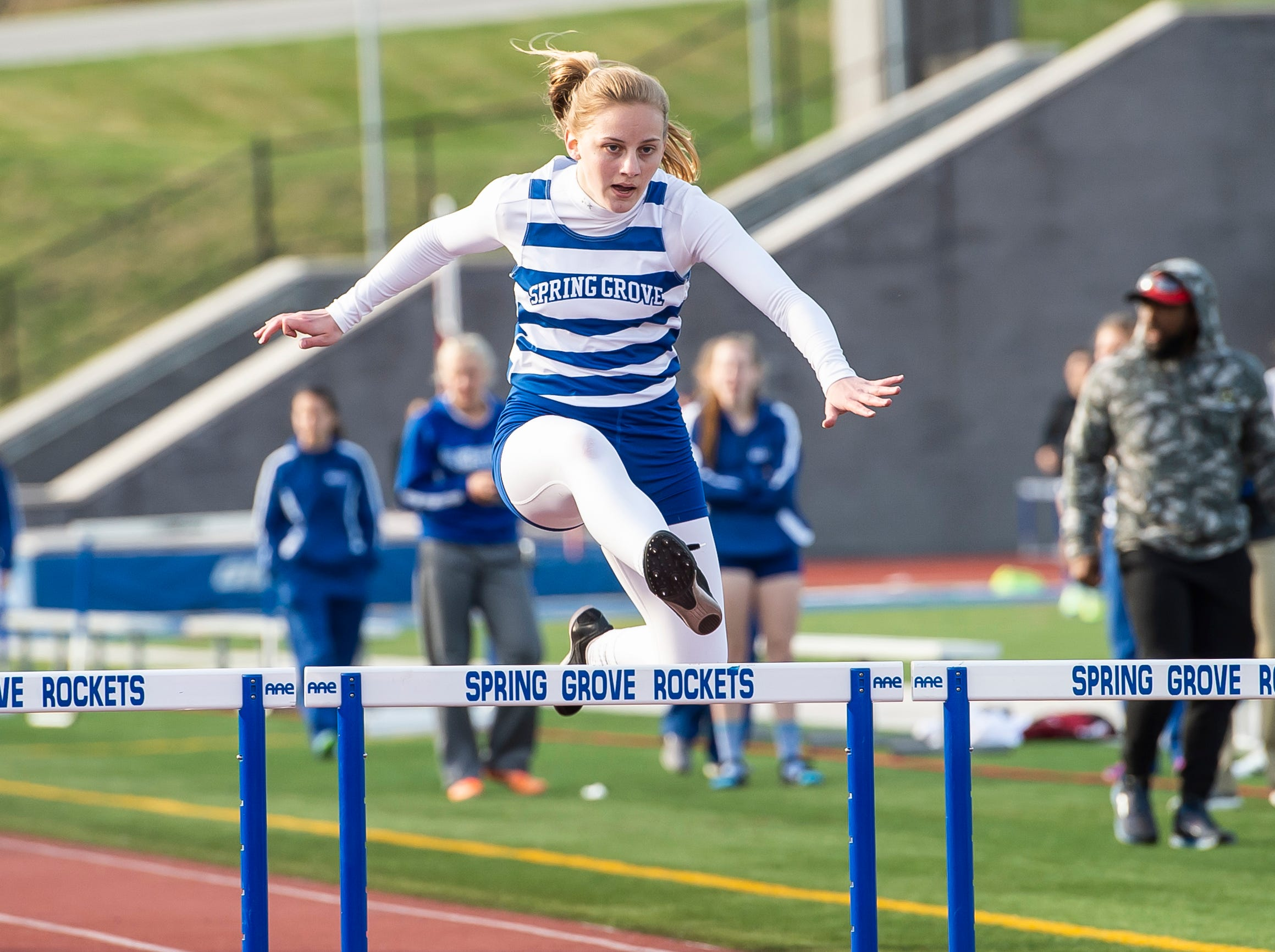 Spring Grove's Sophia Kline leaps over the final hurdle in the 300m hurdles on her way to place first during a track and field meet against South Western on Thursday, April 11, 2019.