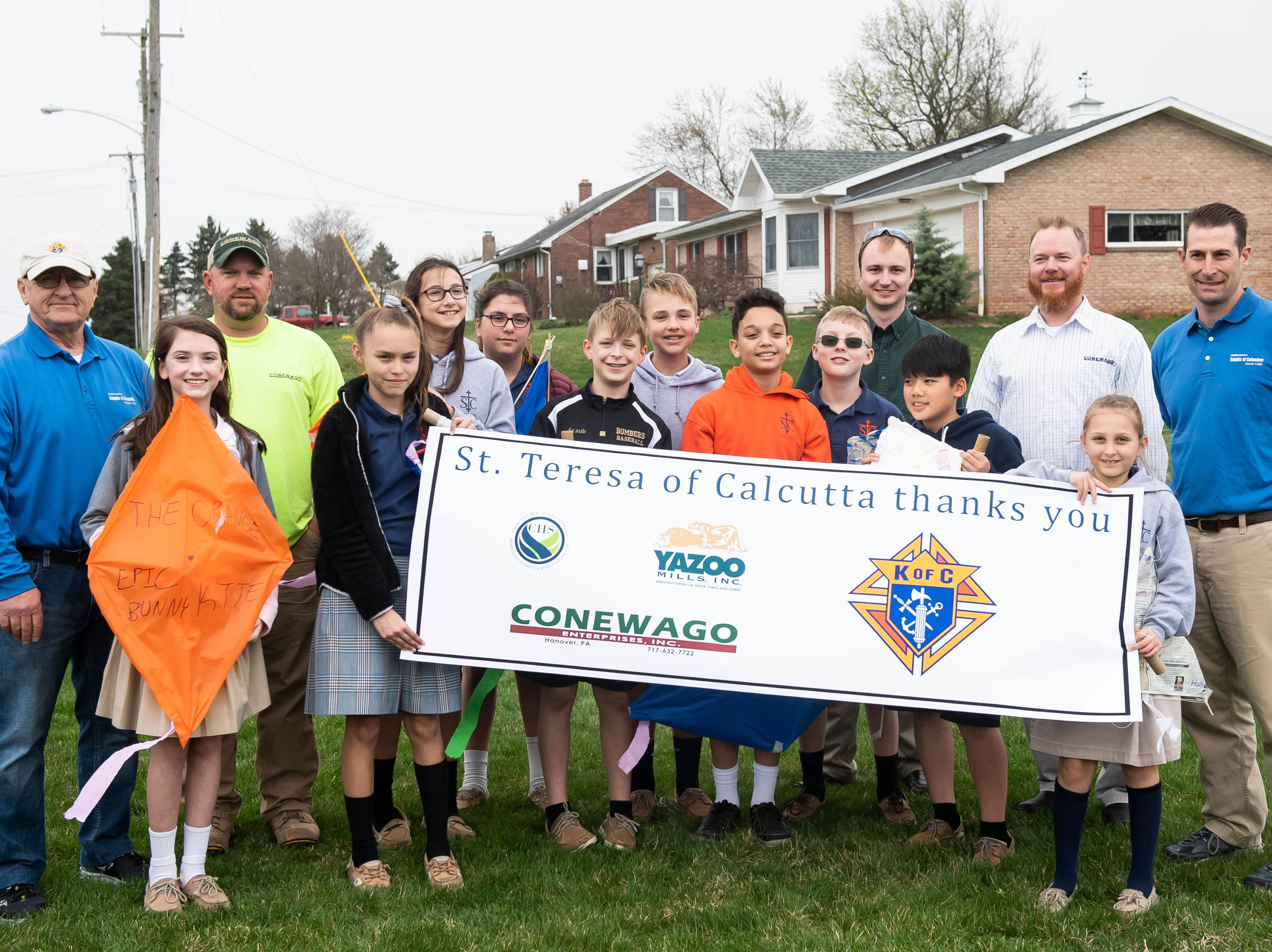 Students from St. Teresa of Calcutta Catholic School pose with a banner thanking the sponsor of their kite day at the school's Conewago campus on Friday, April 12, 2019. The majority of the materials used to make the kites came through donations.