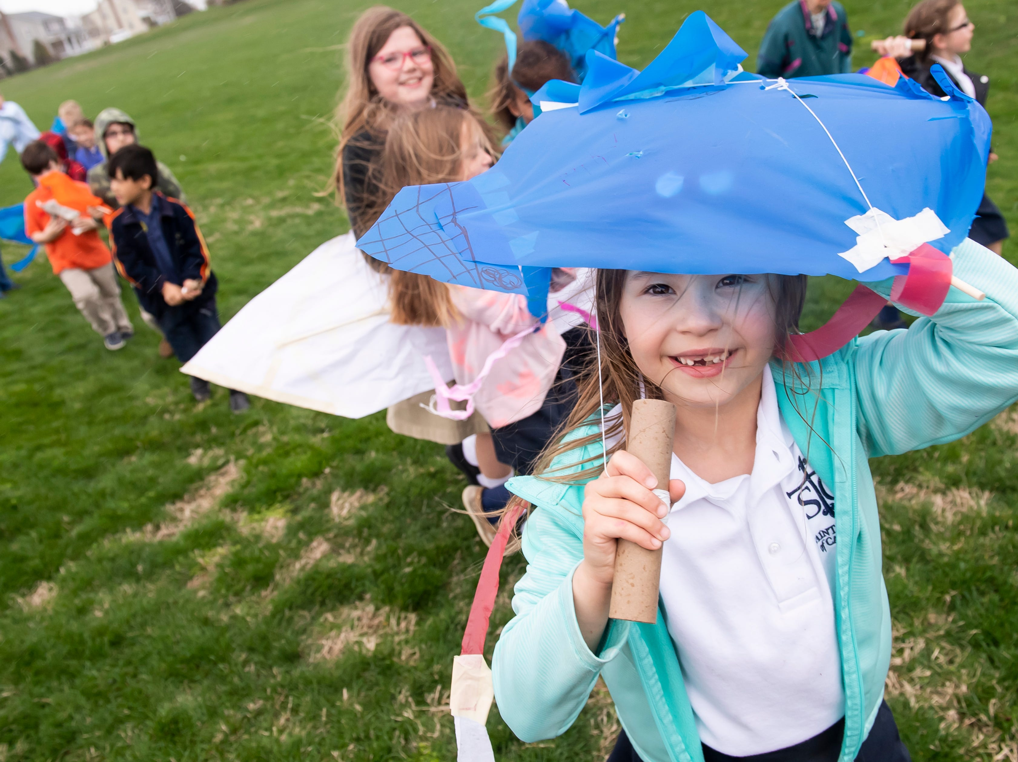 Students from St. Teresa of Calcutta Catholic School use their homemade kites to shield themselves from the rain following a special kite day at the school's Conewago campus on Friday, April 12, 2019.