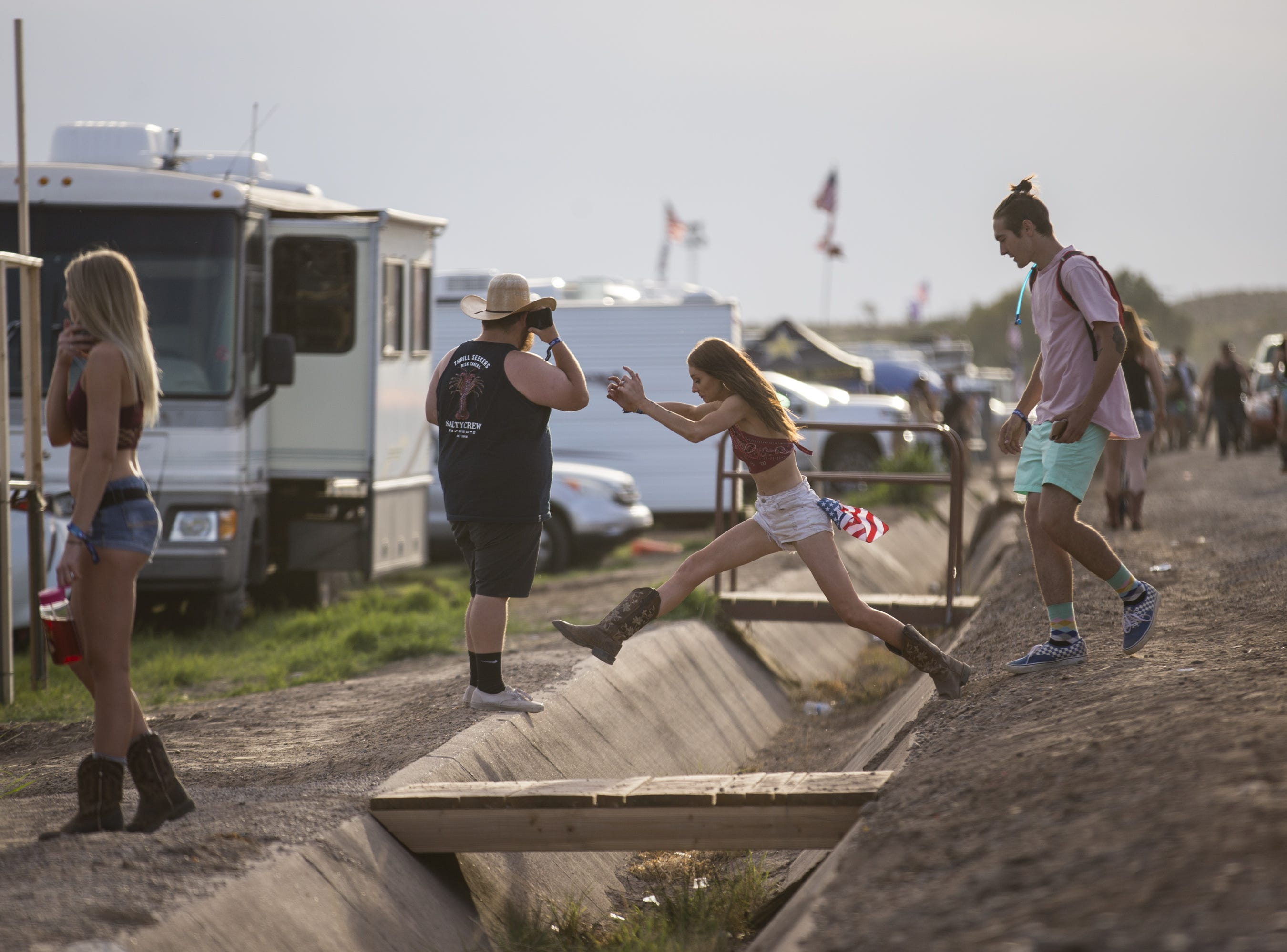 Festival-goers cross a drainage ditch on April 11, 2019, during Day 1 of Country Thunder Arizona in Florence.