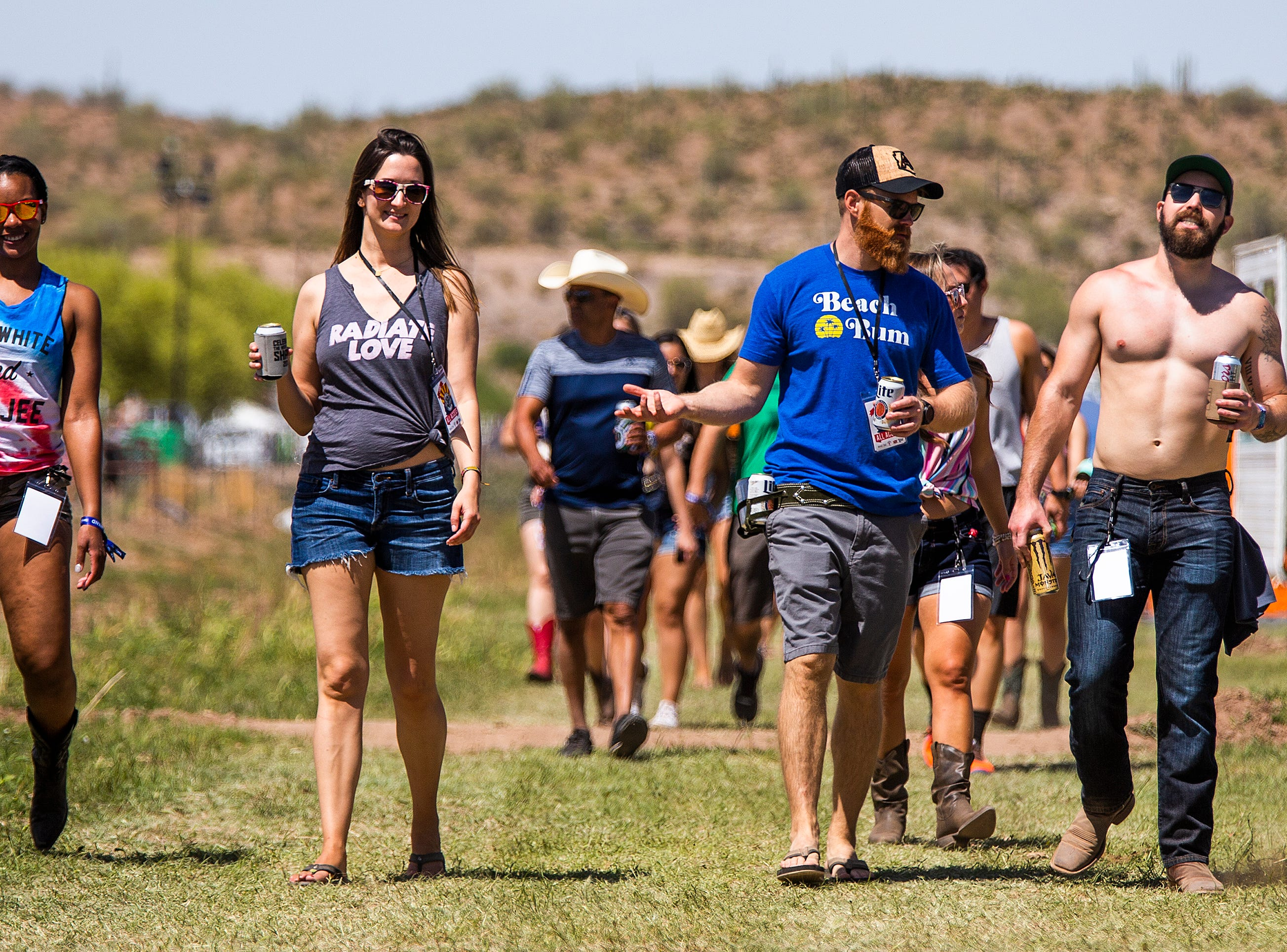 Country music fans walk through camp at the Country Thunder Arizona 2019 music festival outside Florence, Thursday, April 11, 2019.