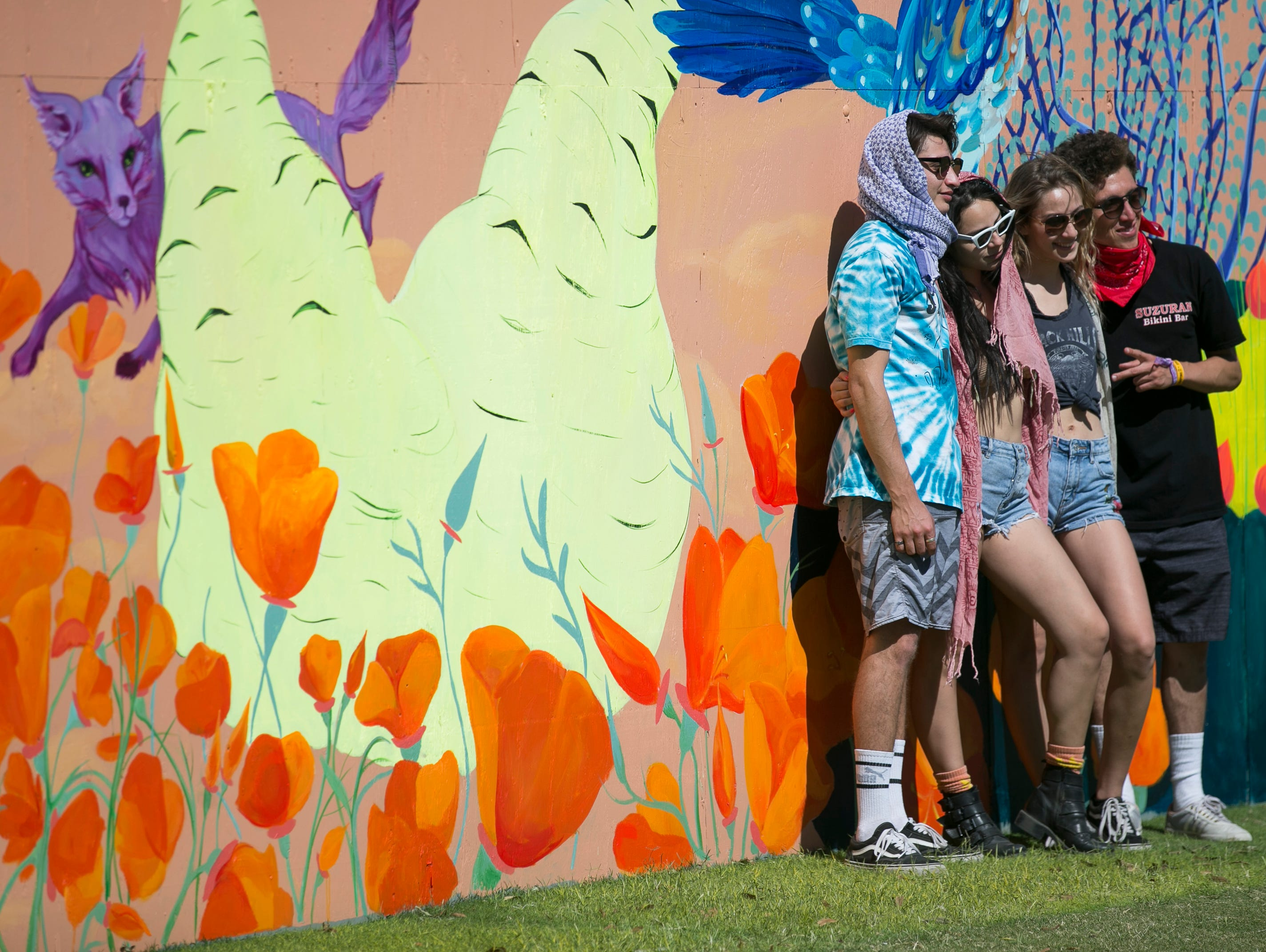 Festival-goers pose in front of a mural near the lobby at the Coachella Valley Music and Arts Festival in Indio, California, on April 11, 2019.