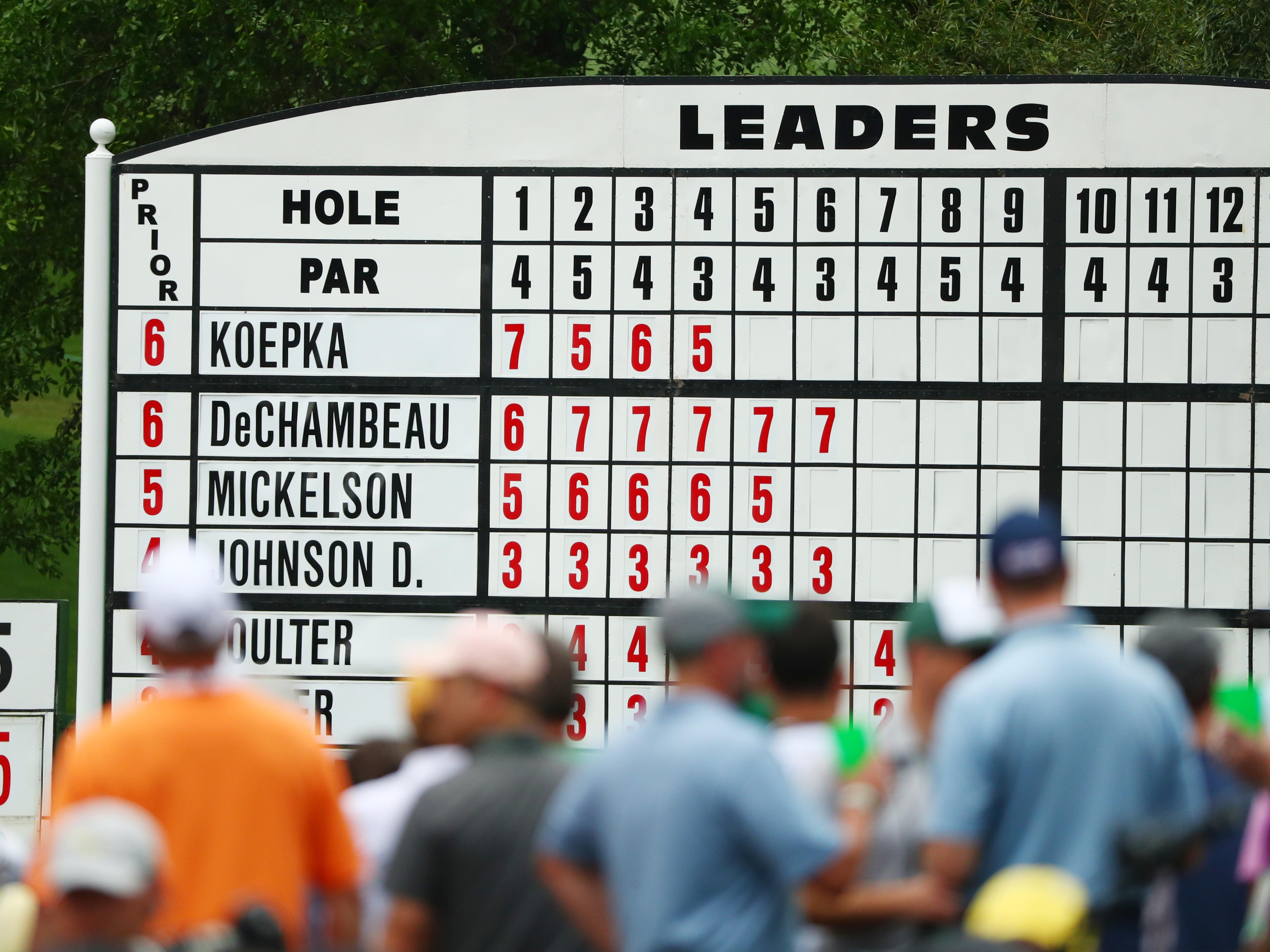 Apr 12, 2019; Augusta, GA, USA; Patrons walk past the leaderboard on the 6th hole during the second round of The Masters golf tournament at Augusta National Golf Club. Mandatory Credit: Rob Schumacher-USA TODAY Sports