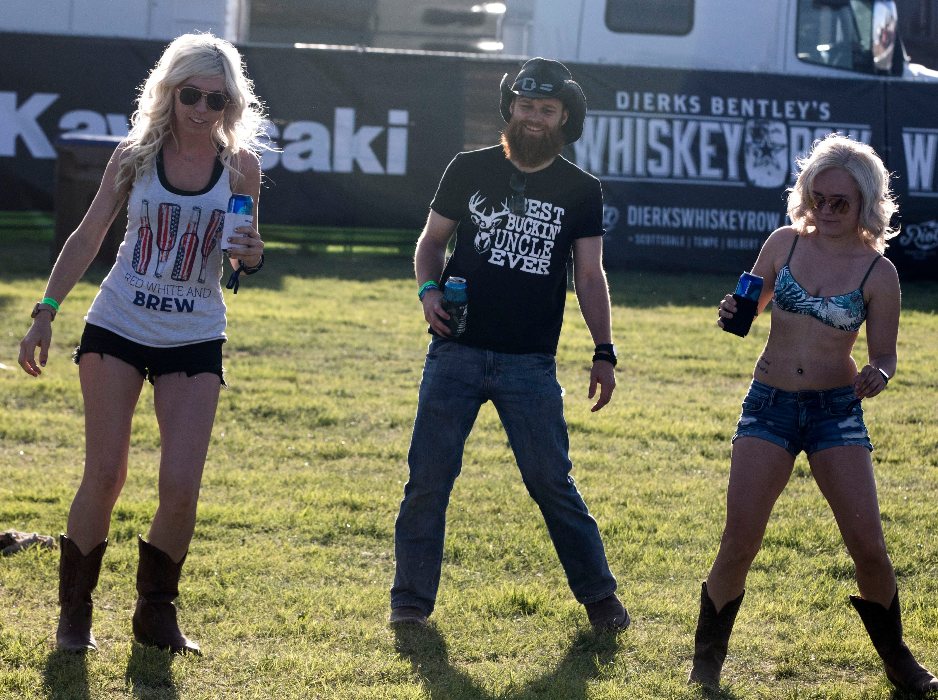 Tiffani Brooks, Brad Eckburg and Brittany Bowman dance as the sun prepares to set during Country Thunder Arizona on April 11, 2019, in Florence, Arizona.