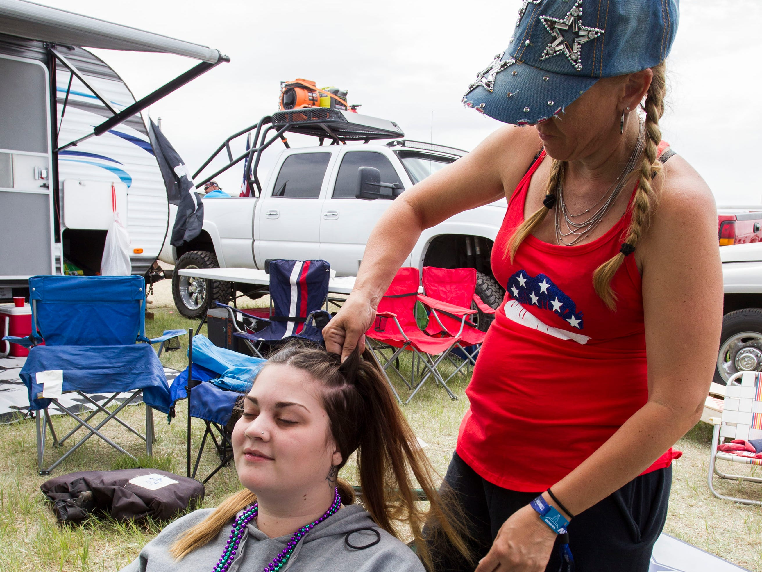 Sharon Payan of Peoria does Prescott's Hailee O'Driscoll's  hair as the day begins out in Country Thunder Arizona on April 12, 2019, in Florence, Ariz.