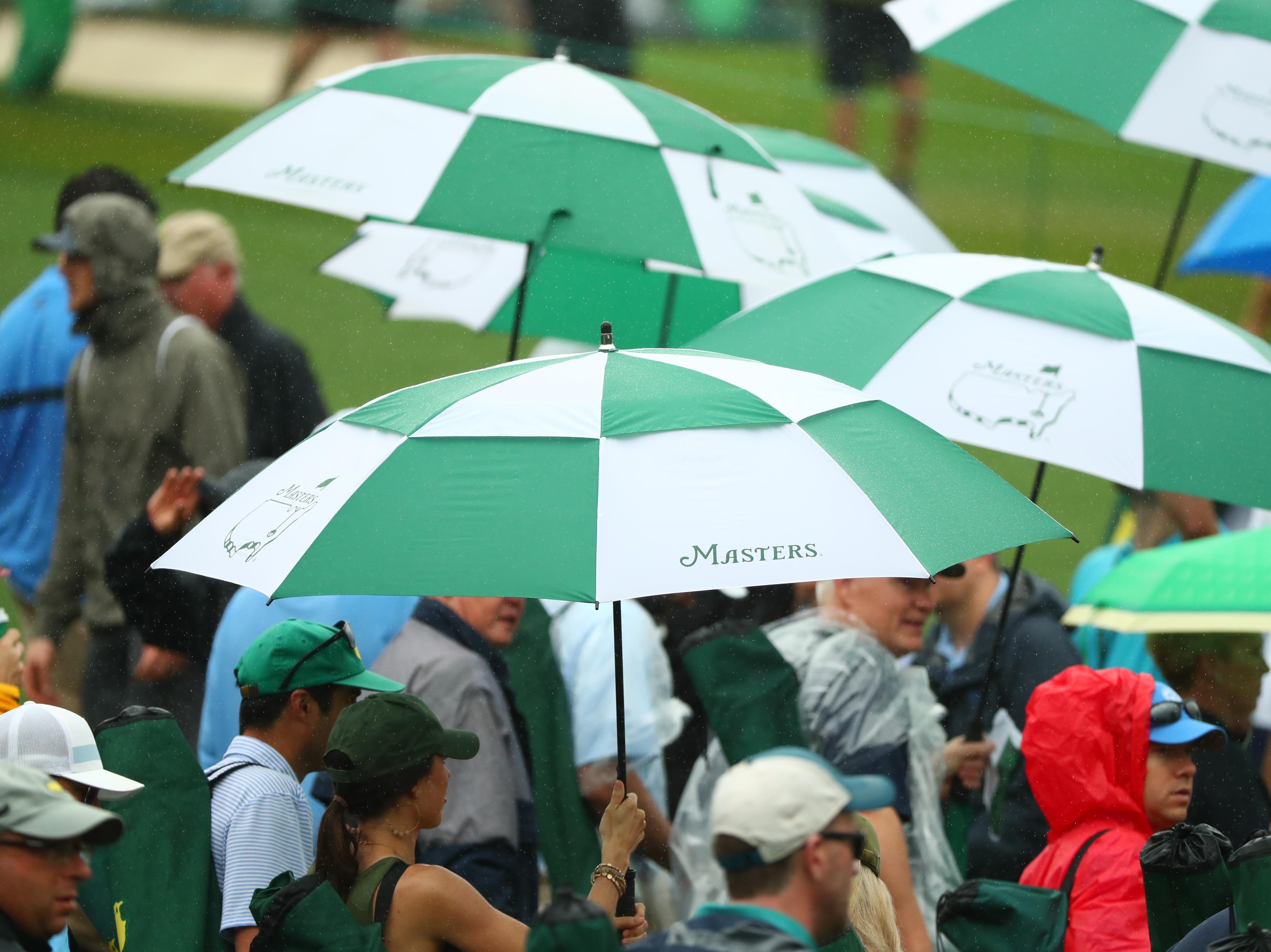 Apr 12, 2019; Augusta, GA, USA; Patrons make their way around the course under umbrellas in the rain during the second round of The Masters golf tournament at Augusta National Golf Club. Mandatory Credit: Rob Schumacher-USA TODAY Sports