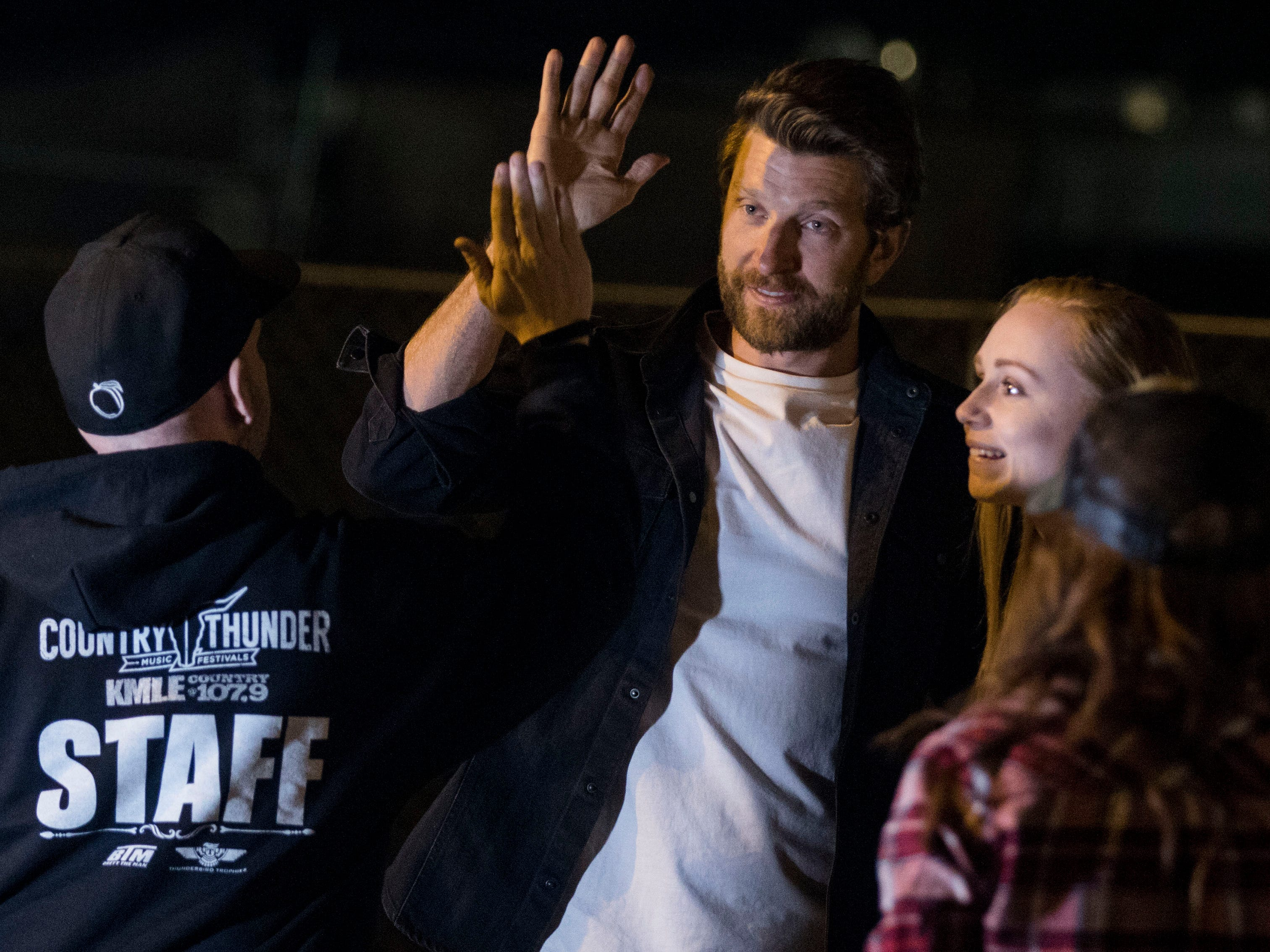 Country superstar Brett Eldredge high-fives his competitor after a game of cornhole with a lucky young lady. Kayla Coffey of Tucson was picked from the audience for the chance meeting with Eldredge while at Country Thunder Arizona on April 11, 2019, in Florence, Ariz.