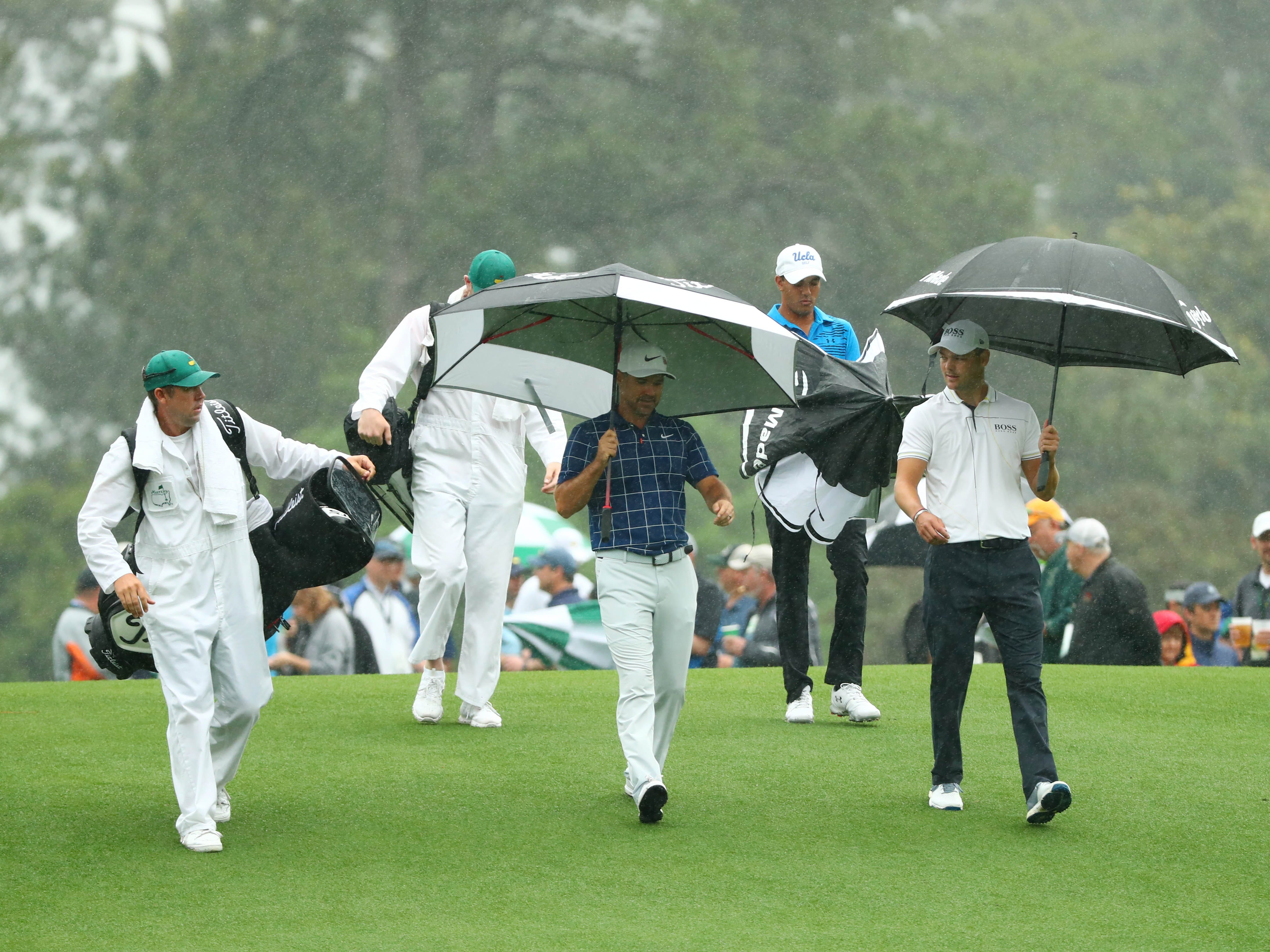 Apr 12, 2019; Augusta, GA, USA; From right Martin Kaymer , Devon Bling and Trevor Immelman walk off the 1st tee under umbrellas during the second round of The Masters golf tournament at Augusta National Golf Club. Mandatory Credit: Rob Schumacher-USA TODAY Sports