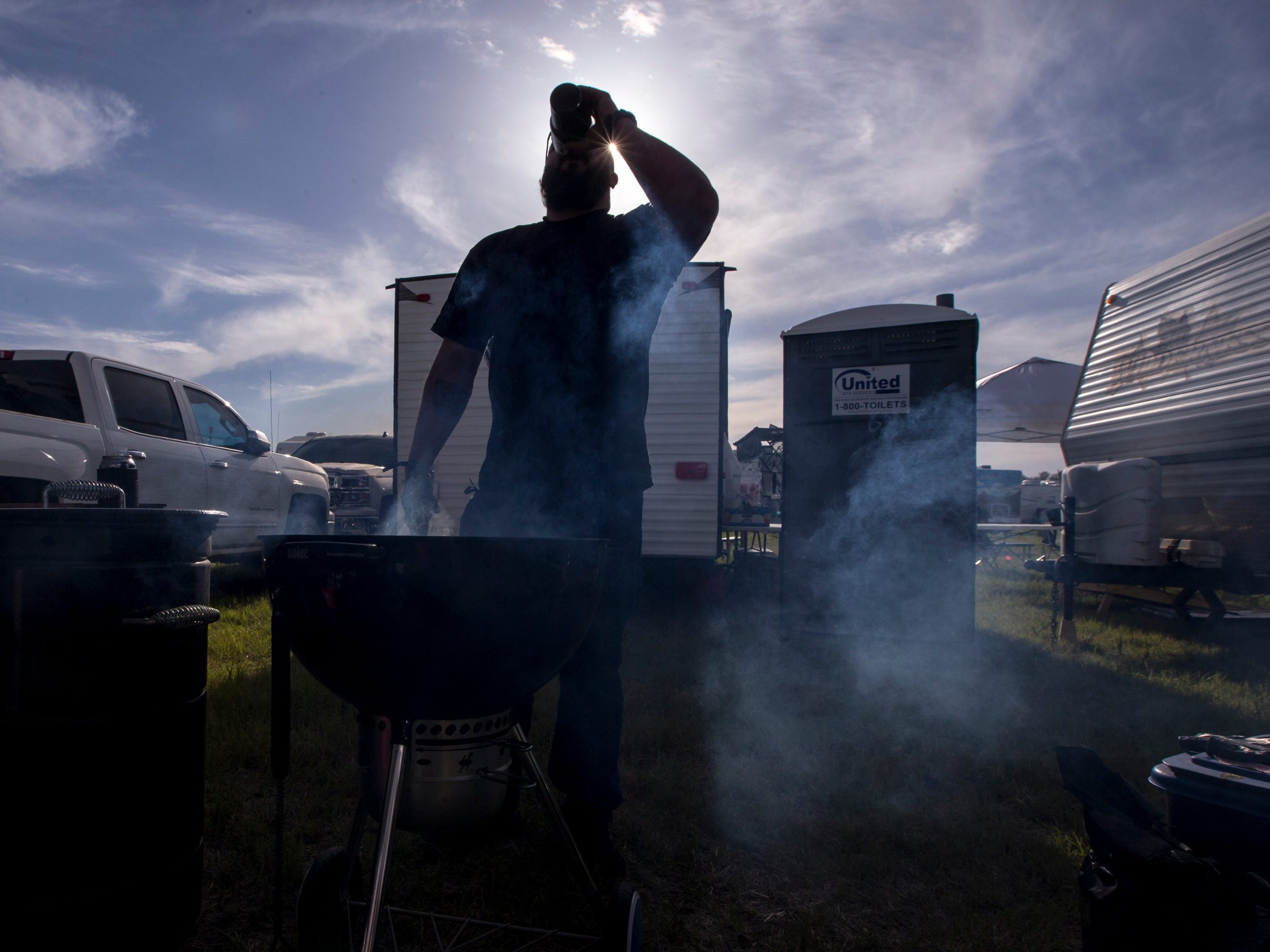 Ernesto Torres drinks a beer while grilling at his campsite during Day 1 of Country Thunder Arizona in Florence, Ariz., on Apr. 11, 2019.